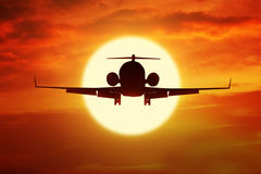 Aeroplane flies on the sky at sunset time Stock Photography