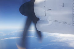 Aeroplane flying over the ocean and turbine detail in movement Royalty Free Stock Images