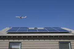Aeroplane Flying Over Rooftop With Solar Panels Royalty Free Stock Images