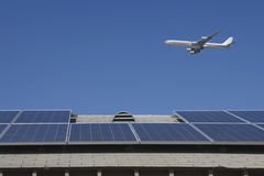Aeroplane Flying Over Rooftop With Solar Panels Stock Photos