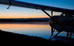 Aeroplane at the lake. A silhouetted aeroplane standing at the sunset lake royalty free stock photos