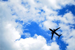 Aeroplane in the sky flying above. The sky is blue and cloudy Stock Image