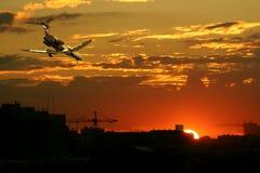 Aeroplane at sunset. Aeroplane flying over city at sunset royalty free stock image