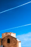 Aeroplane trails above old warehouse in blue sky Stock Photography