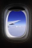 Aeroplane window with blue skies Royalty Free Stock Photography