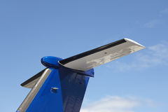 Aeroplane wing tale viewed from below with blue sky Royalty Free Stock Photos