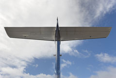 Aeroplane wing tale viewed from below with blue sky Stock Photos