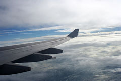 Aeroplane wings over clouds Stock Photo