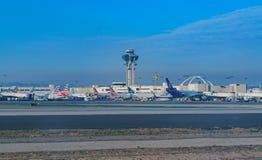 Aeroplani che coltivano a gradini all'aeroporto internazionale occupato di Los Angeles immagine stock