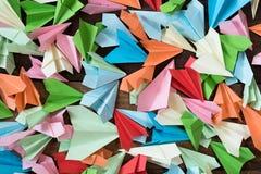 Aeroplani di carta variopinti sul fondo di legno della tavola fotografie stock libere da diritti