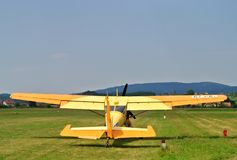 Aeroplano amarillo-naranja del deporte durante sacar en pista en el campo de aviación del deporte imagen de archivo