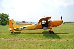 Aeroplano amarillo-naranja del deporte en pista en el campo de aviación del deporte fotografía de archivo