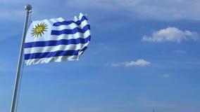 Aeroplano che sorvola bandiera d'ondeggiamento dell'Uruguay video d archivio