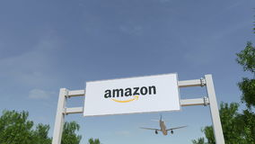 Aeroplano che sorvola il tabellone per le affissioni di pubblicità con Amazon logo di COM 3D editoriale che rende clip 4K archivi video
