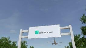Aeroplano che sorvola il tabellone per le affissioni di pubblicità con il logo di BNP Paribas 3D editoriale che rende clip 4K illustrazione di stock