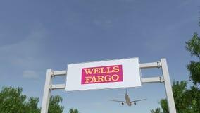Aeroplano che sorvola il tabellone per le affissioni di pubblicità con il logo di Wells Fargo 3D editoriale che rende clip 4K archivi video