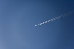 aeroplano che vola su nel cielo con le scie di condensazione Fotografia Stock