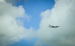 Aeroplano che vola via al cielo blu Fotografia Stock