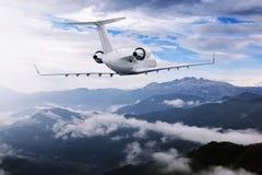 Aeroplano che vola vicino alle alte montagne ed alle nuvole Immagine Stock Libera da Diritti