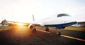 Aeroplano comercial blanco que se coloca en la pista del aeropuerto en la puesta del sol La vista delantera del aeroplano del pas foto de archivo libre de regalías