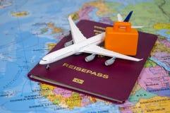 Aeroplano con un passaporto tedesco su una mappa di mondo fotografia stock libera da diritti