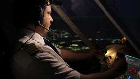 Aeroplano de navegación del comandante profesional de la tripulación aérea sobre ciudad en la noche almacen de metraje de vídeo
