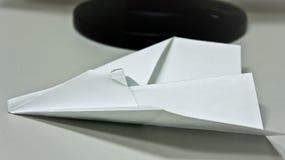 Aeroplano de papel en la tabla imagenes de archivo