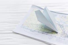 Aeroplano de papel, en un mapa en un fondo de madera fotografía de archivo libre de regalías