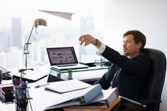 Aeroplano de papel que lanza acertado del oficinista del hombre que sueña despierto foto de archivo libre de regalías