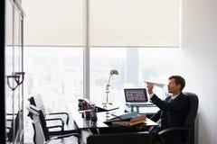 Aeroplano de papel que lanza agujereado del hombre de negocios en oficina imagen de archivo