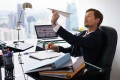 Aeroplano de papel que lanza agujereado del trabajador no manual en oficina foto de archivo