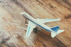 Aeroplano del giocattolo sopra la tavola strutturata di legno Retro immagine di stile Immagine Stock