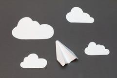 Aeroplano del Libro Bianco con le nuvole su un fondo grigio Immagini Stock Libere da Diritti