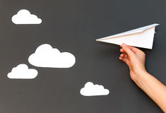 Aeroplano del Libro Blanco con las nubes en un fondo gris Imagen de archivo libre de regalías