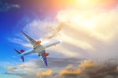 Aeroplano del pasajero en la nube de la luz del sol inusual de la forma y de la puesta del sol entre las nubes recorrido por tran fotografía de archivo