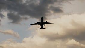 Aeroplano del pasajero que saca en la puesta del sol contra la perspectiva de las nubes muy hermosas Imagen de archivo libre de regalías