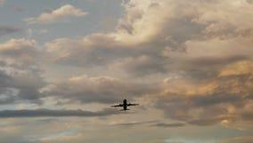 Aeroplano del pasajero que saca en la puesta del sol contra la perspectiva de las nubes muy hermosas Foto de archivo libre de regalías