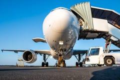 Aeroplano del passeggero con le scale aperte del compartimento e di imbarco di bagagli al grembiule dell'aeroporto Fotografie Stock