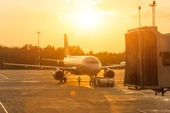 Aeroplano del passeggero durante di spinta l'operazione indietro, uguagliante aeroporto al tramonto fotografia stock libera da diritti