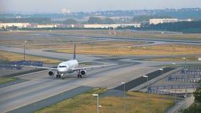 Aeroplano del ` s de Lufthansa que lleva en taxi después de aterrizar Boeing 777 que aterriza en el fondo almacen de metraje de vídeo