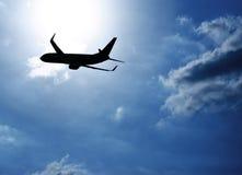 Aeroplano della siluetta in cielo blu Fotografia Stock