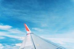 Aeroplano delle nuvole, del cielo e dell'ala come finestra vista attraverso di un aereo Immagine Stock