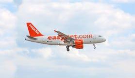 Aeroplano di easyJet prima dell'atterraggio/dopo il decollo, cielo con le nuvole Fotografia Stock