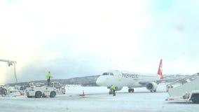 Aeroplano di Helvetic Airways Embraer 190 su un aeroporto nevoso di Tromso video d archivio
