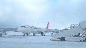 Aeroplano di Helvetic Airways Embraer 190 su un aeroporto nevoso di Tromso archivi video