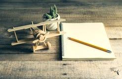 Aeroplano di legno del giocattolo con il taccuino e la matita in bianco sulla tavola di legno Fotografia Stock