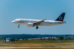 Aeroplano di linee aeree di alleanza della stella che prepara per l'atterraggio al tempo di giorno in aeroporto internazionale fotografie stock
