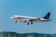 Aeroplano di linee aeree di alleanza della stella che prepara per l'atterraggio al tempo di giorno in aeroporto internazionale immagini stock libere da diritti