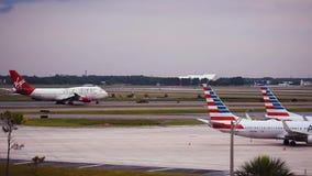 Aeroplano di Virgin Atlantic che scivola sulla pista e sulla vista parziale degli aeroplani di American Airlines ad Orlando Inter