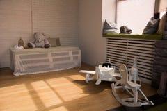 Aeroplano e cavalli di legno del giocattolo sul pavimento nella stanza Fotografia Stock